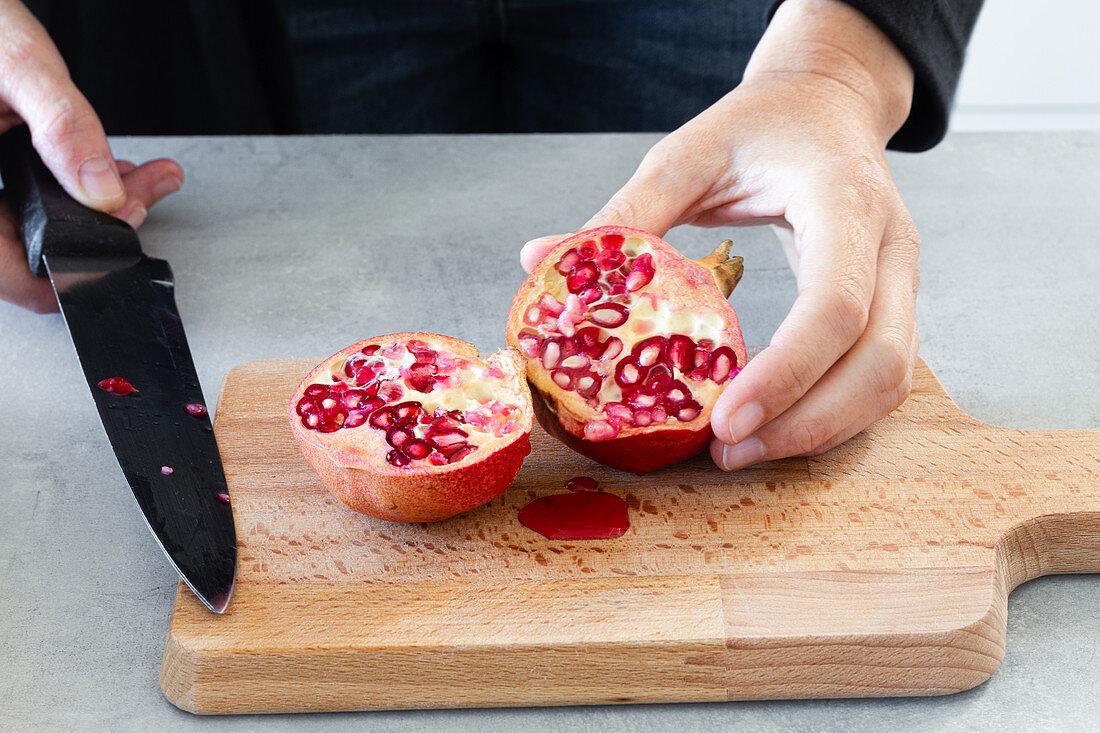 Cutting pomegranate on cutting board