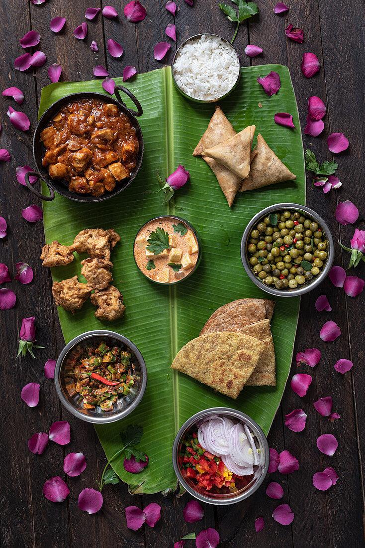 Assorted dishes of Indian cuisine arranged on huge banana leaf