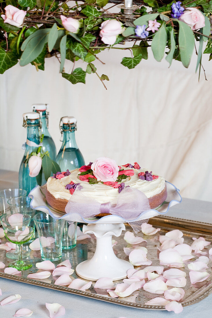 Cake with sugar flowers on a cake stand under a flower wreath
