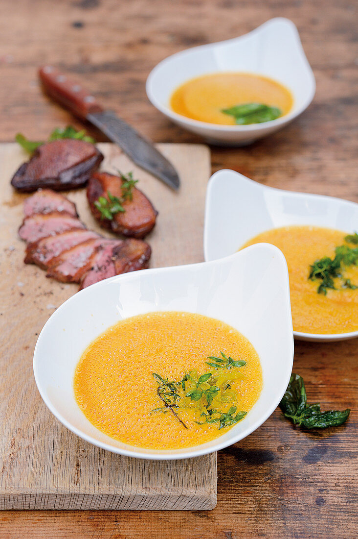 Cream of pumpkin soup with warm smoked wild duck breast