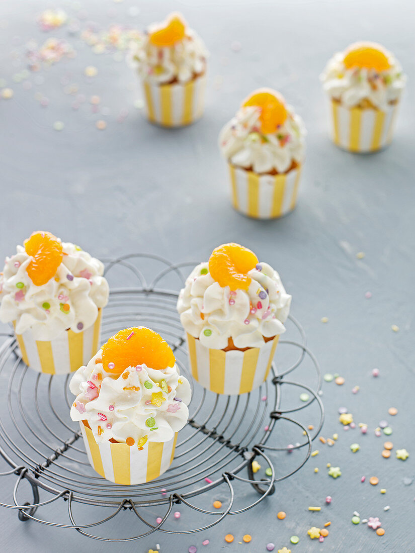 Creamy cheesecake cupcakes with mandarins and colourful sugar sprinkles