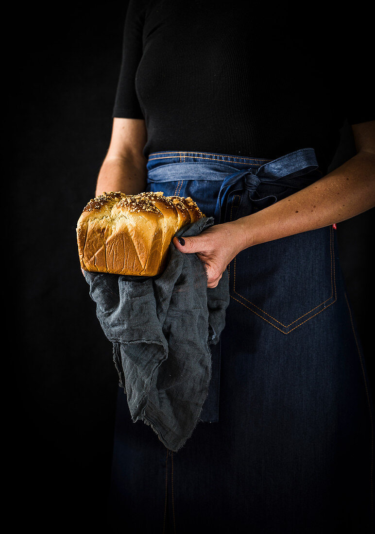 Woman holds freshly baked box-shaped brioche in her hands