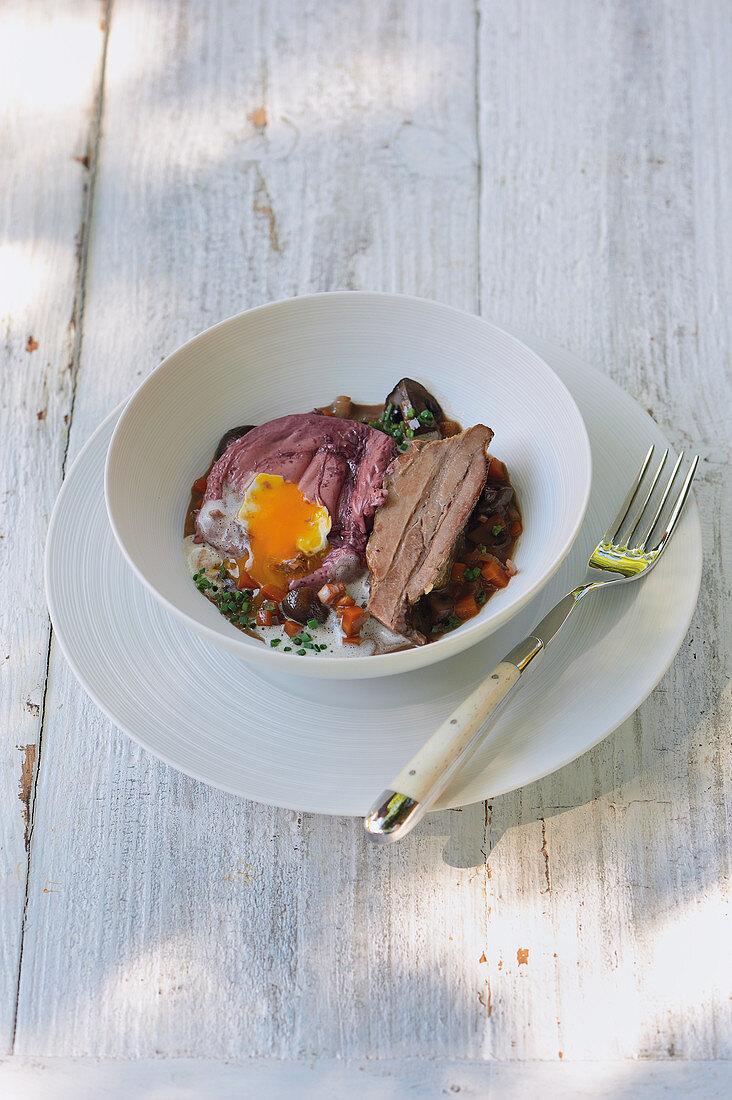 Wild pork belly confit with oeufs en meurette in a bowl