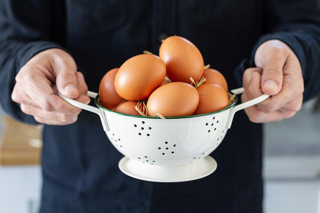 Man holds brown chicken eggs in white colander