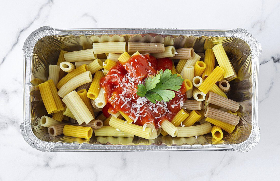 Macaroni with ketchup and cheese in container for takeaway