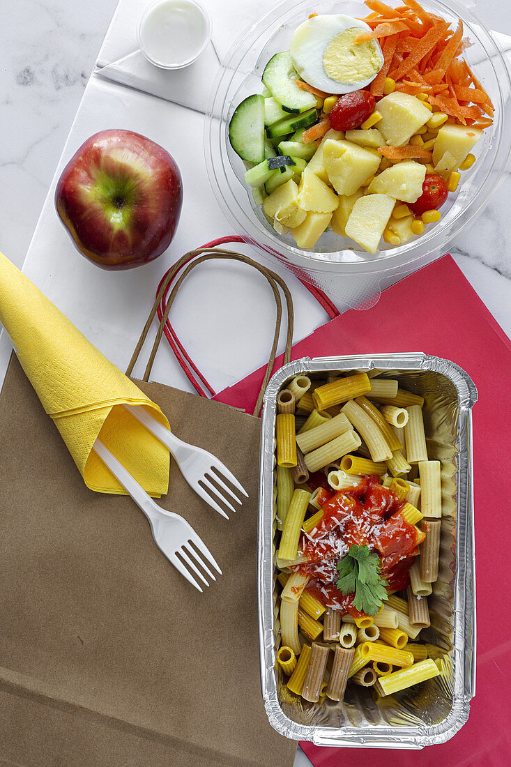 Vegetables with boiled egg and macaroni with ketchup and cheese for takeaway