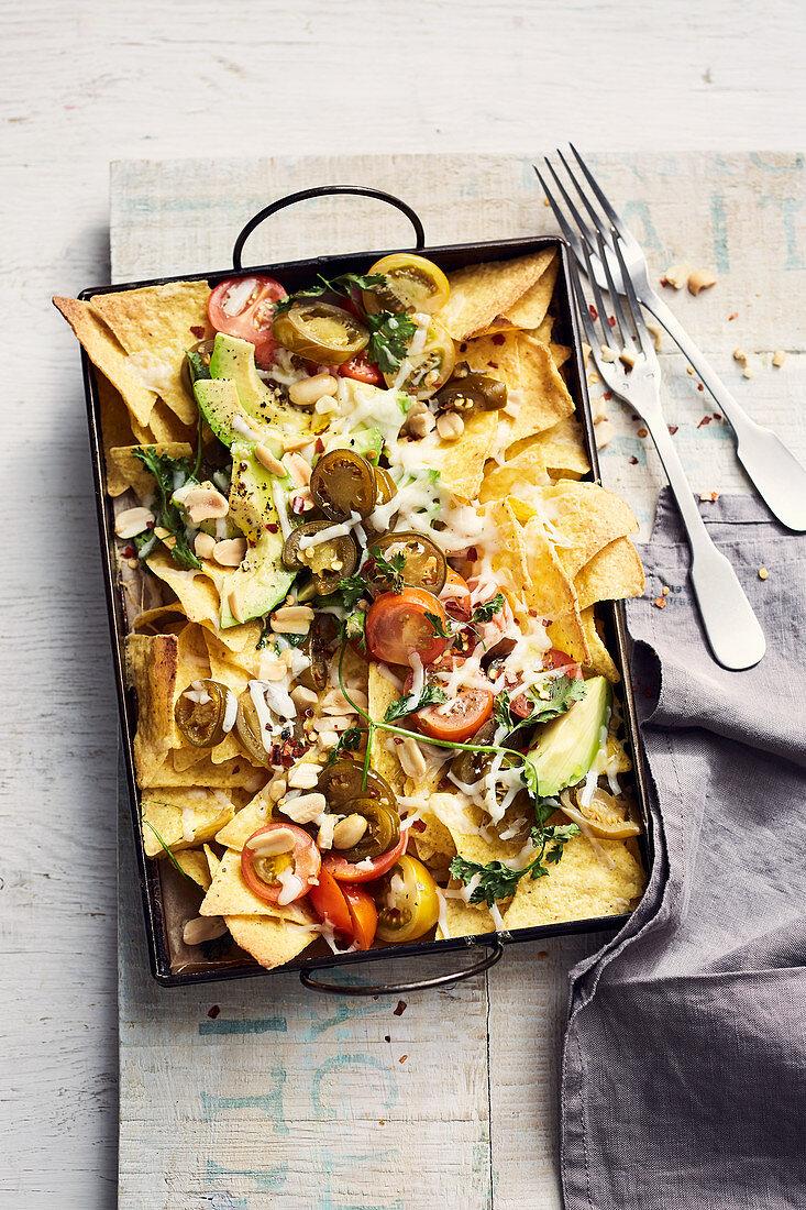 Nachos mit Ziegenkäse, Avocado, Jalapenos, Tomaten, Koriander und Erdnüssen