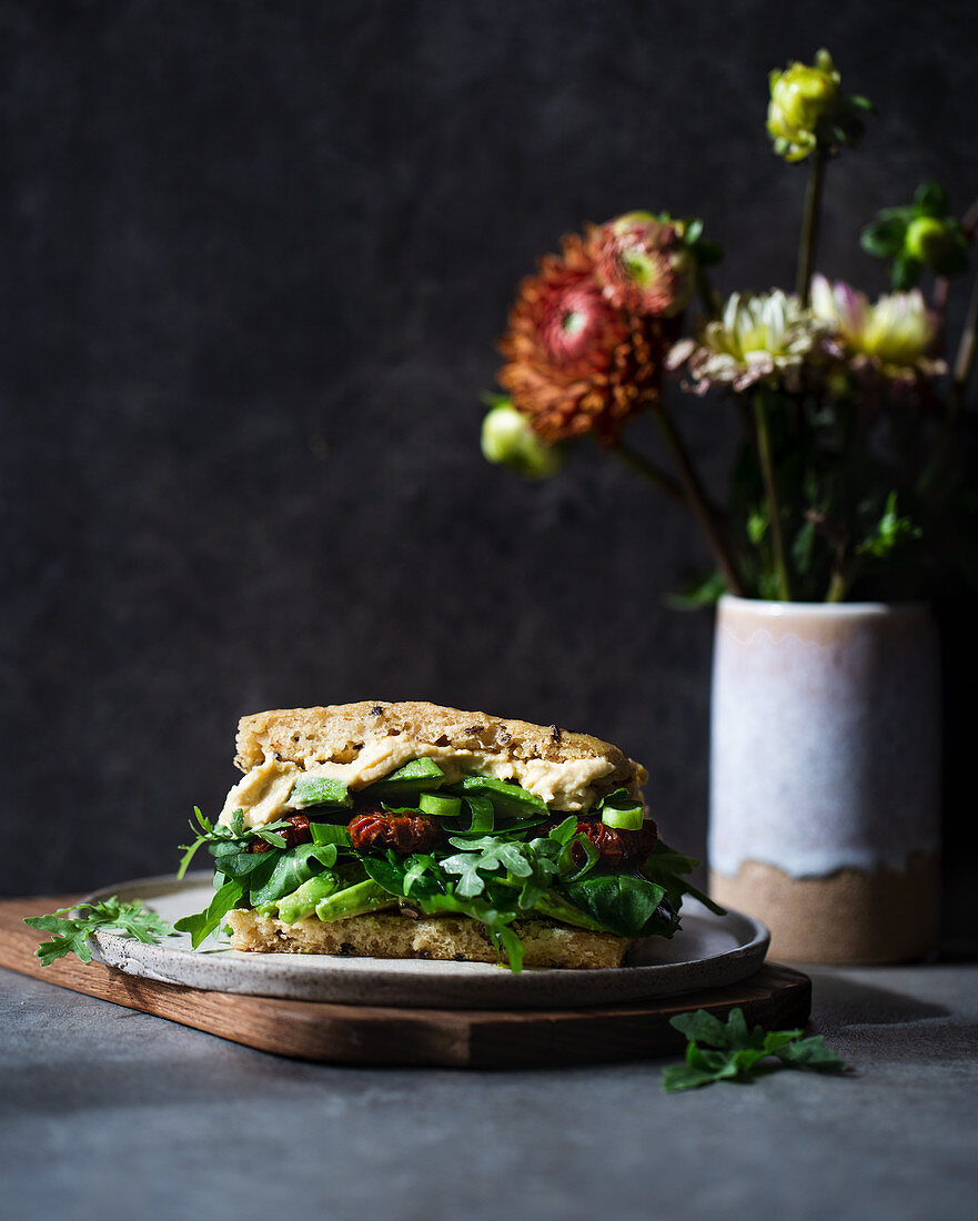 Vegan sandwich filled with hummus, avocado, sundried tomatoes and rocket salad