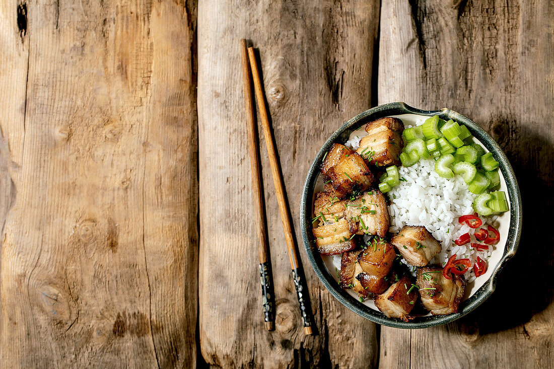 Grilled deep fried pork belly in bowl with rice, celery, chili pepper and spring onion