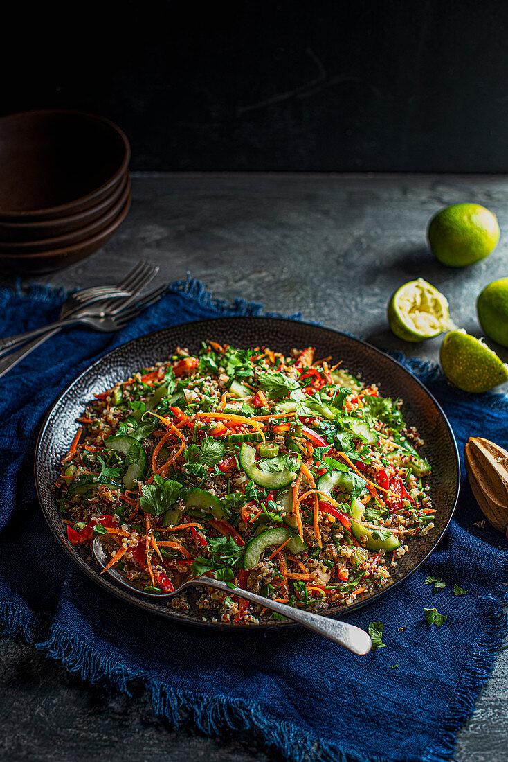 Vegan crunchy quinoa salad with carrot, peppers, coriander, limes, sesame seeds, sesame oil and penut butter dressing