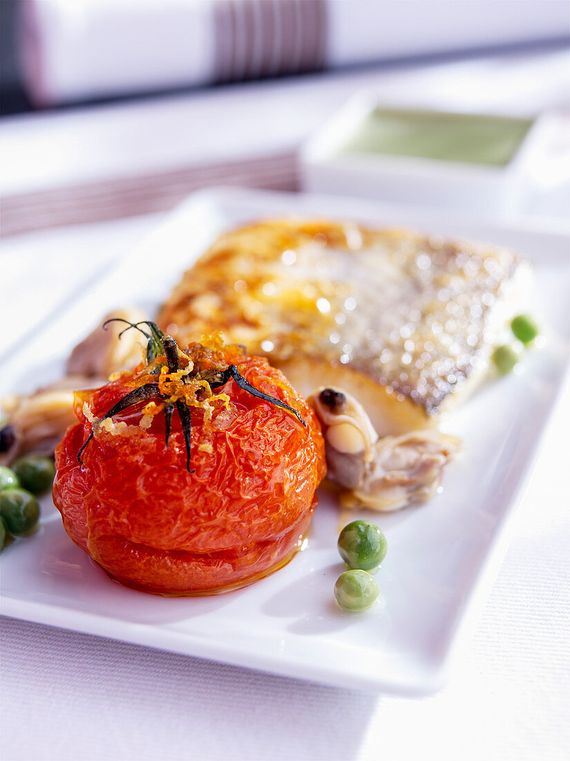 Fried hake with peas and tomato