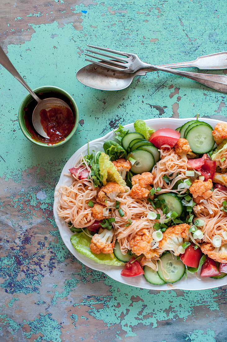Vegan rice noodle salad with cauliflower, lettuce, cucumber, tomatoes and spring onion