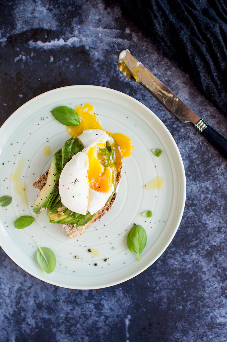 Toast with avocado, poached egg and basil