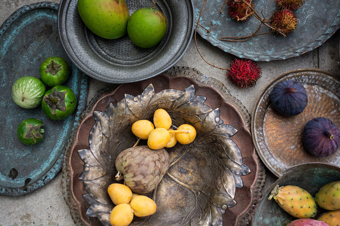 Antique platter and bowls with lychee, custard apple fruits, figs, rambutan lychee, Thai eggplants and mangoes