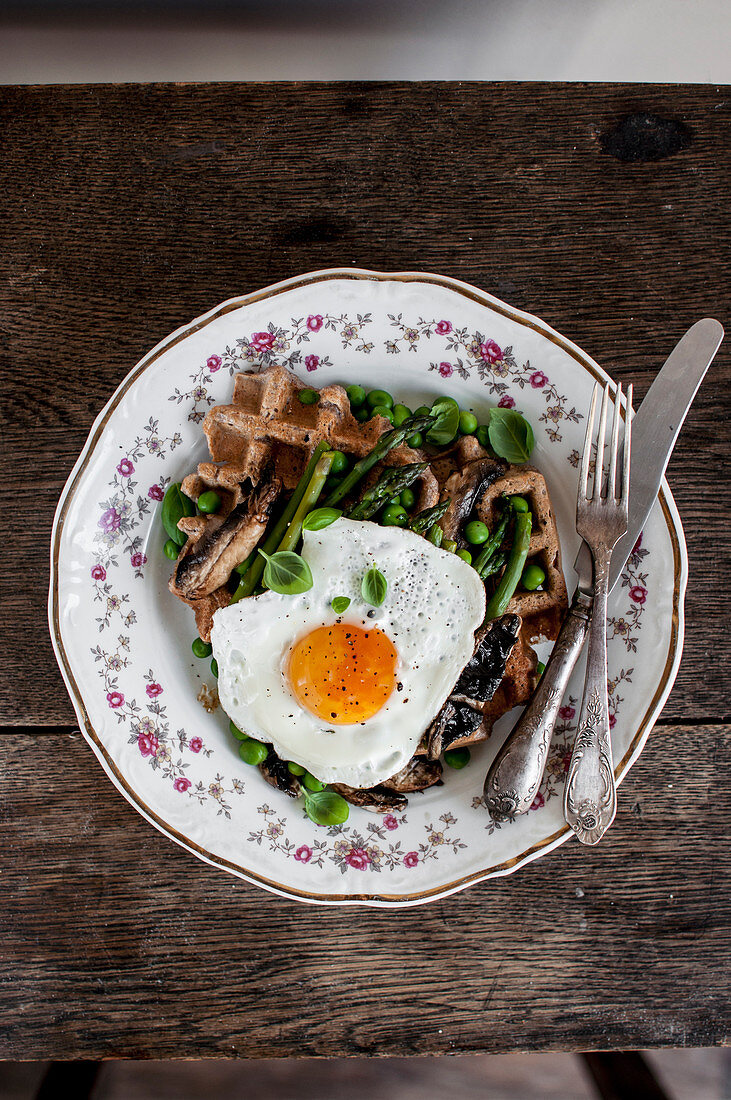 Buckwheat waffle with green asparagus, green peas, fried portobello mushrooms, fried egg and fresh basil leaves