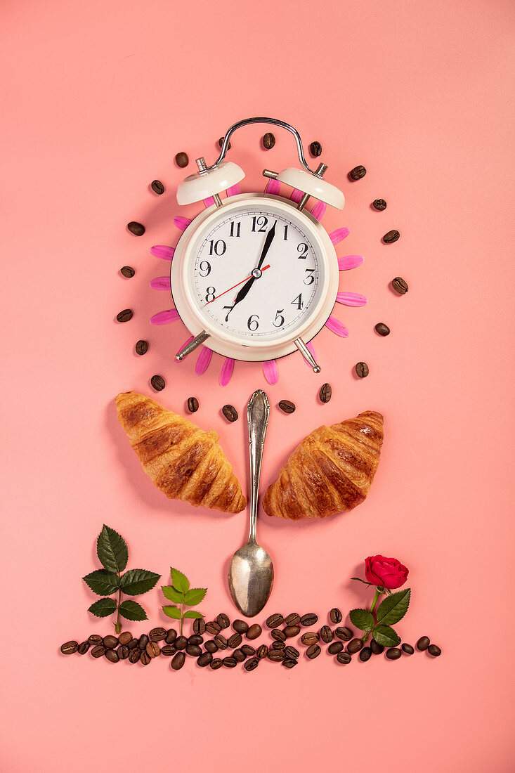 Creative layout made of alarm clock, croissants, coffee, spoon and flowers