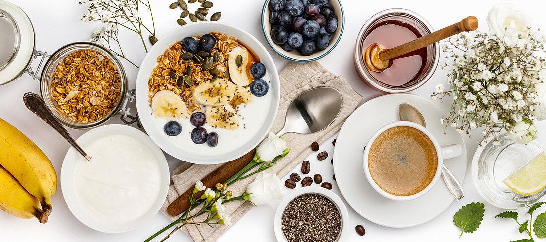 Healthy breakfast with granola, yogurt, coffee, fruits and chia seeds