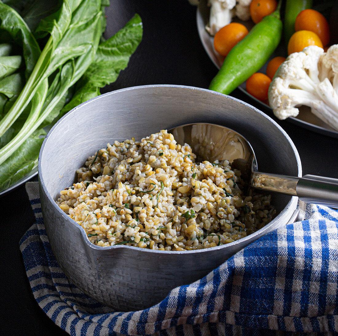 Levante Küche: Freekeh (gekochter, grüner, junger Weizen) mit Spinat und Knoblauch
