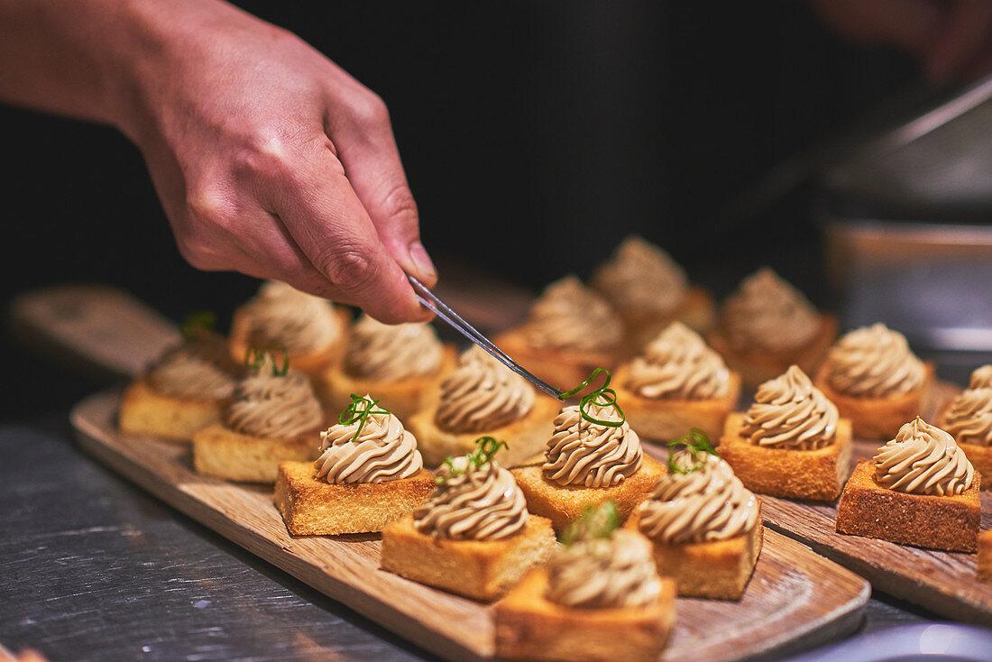 Koch garniert Canape in französischem Restaurant