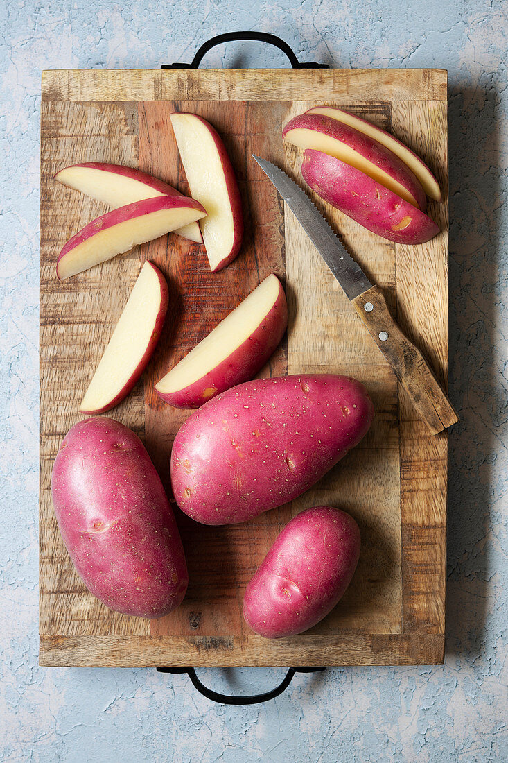 Whole and sliced red potatoes on a wooden cutting board