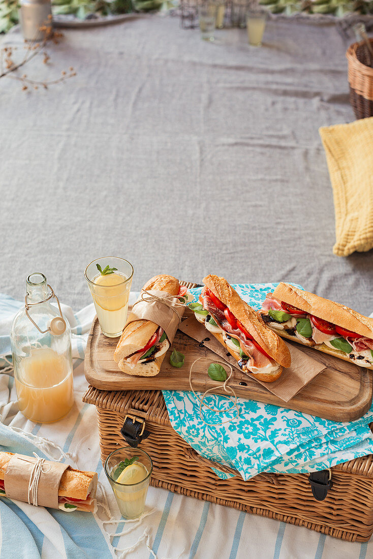 Italian style baguettes filled with mozzarella, prosciutto and tomato packed for picnic
