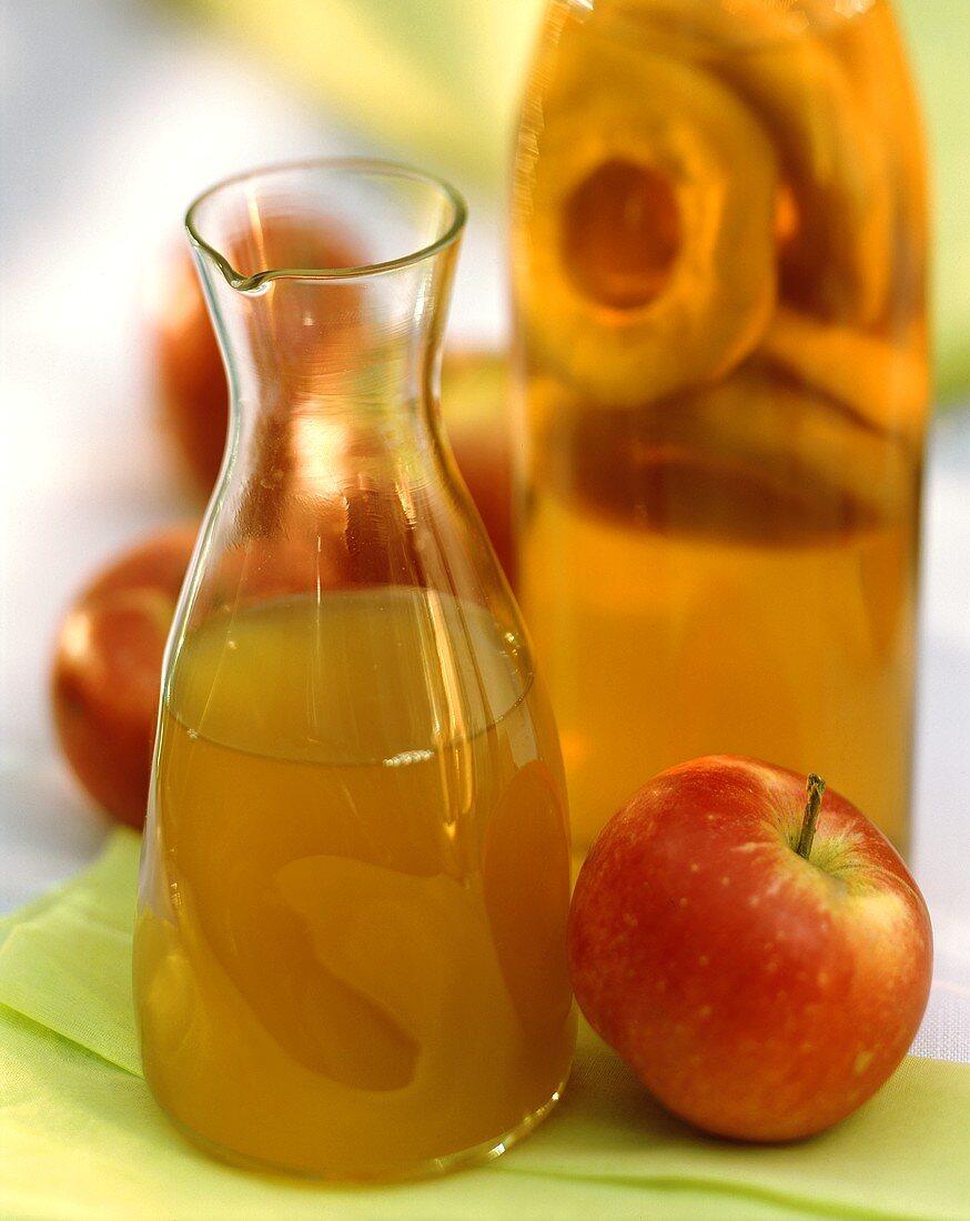 Cider vinegar in glass jug; three apples