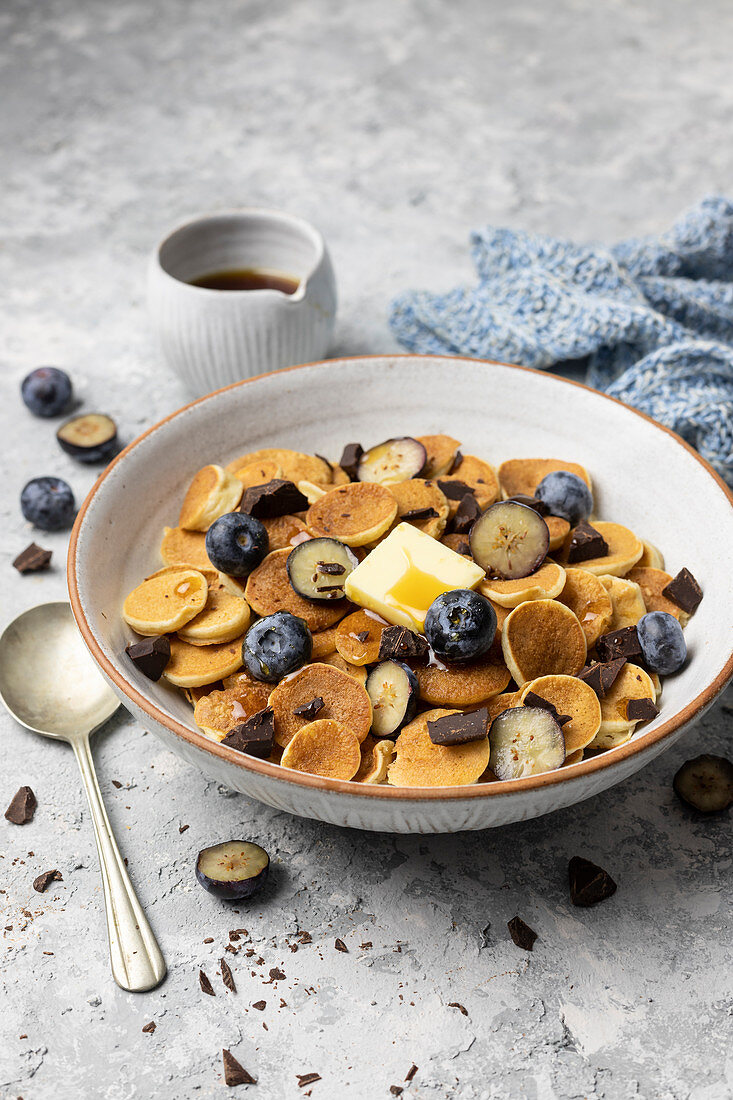 Pancake cereal with blueberries, chocolate, butter and maple syrup