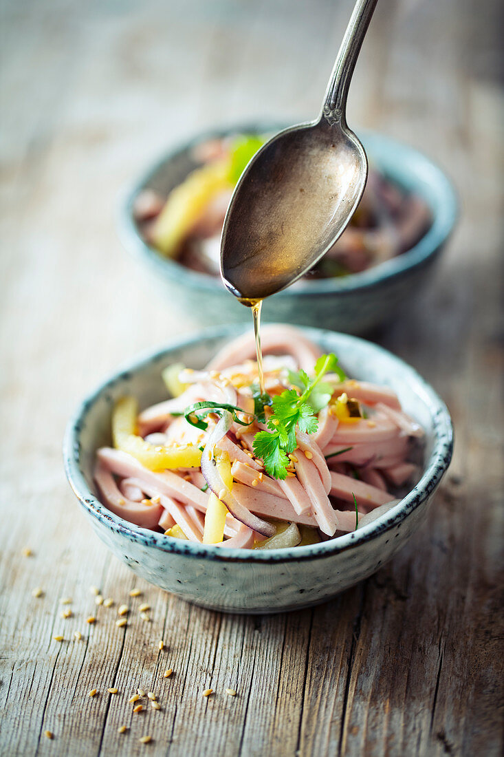 Vegetarian sour and spicy 'sausage salad' with roasted sesame oil and coriander