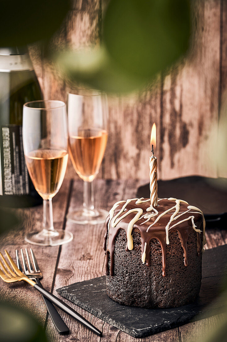 Chocolate cake with burning candle and glasses of champagne