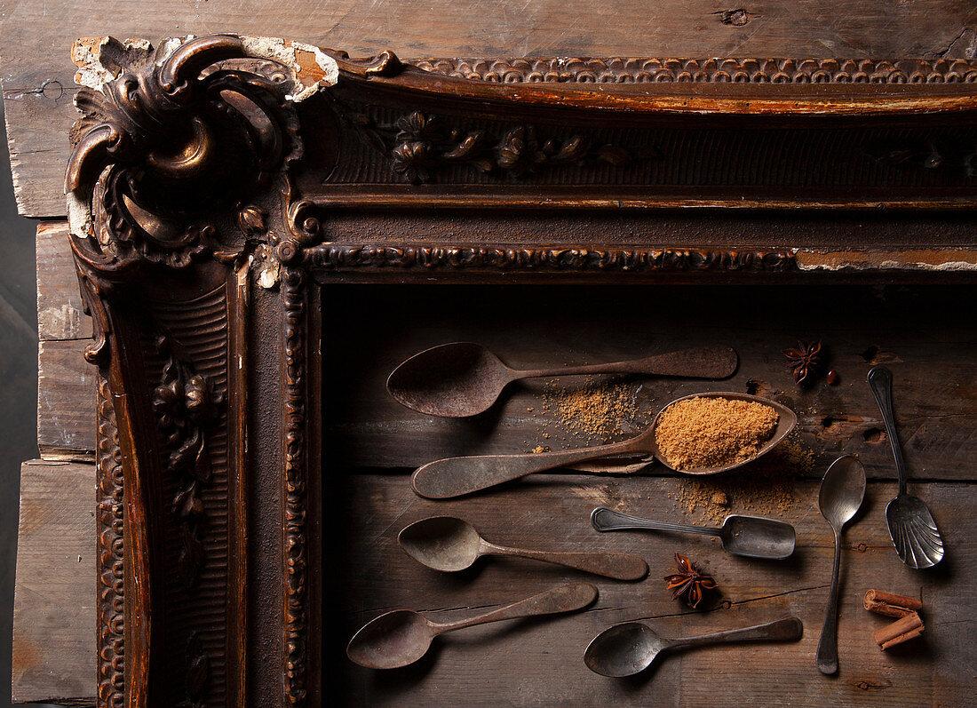 Brauner Zucker, Sternanis, Zimtstangen und antike Löffel