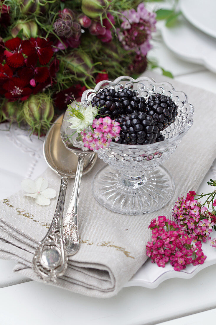 Still life with blackberries in glass bowls, next to a silver spoon and flowers