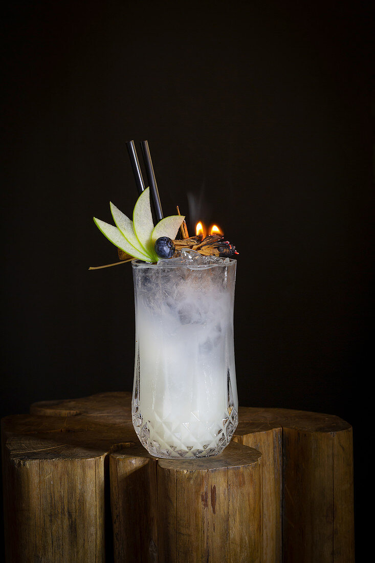 Cocktail garnished with apple slices and burning spices