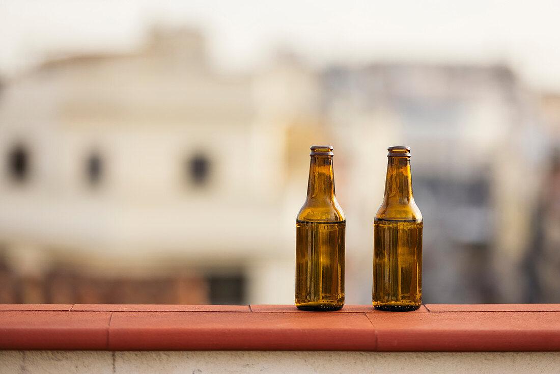 Two beer bottles on balcony wall