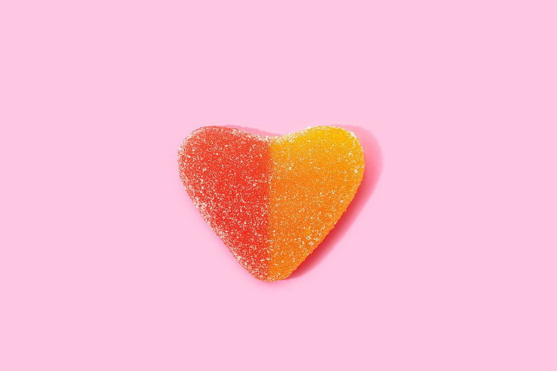 Heart shaped jelly candy on pink surface