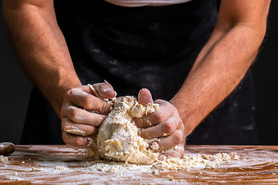 Hands kneading and rolling pile of dough for bread
