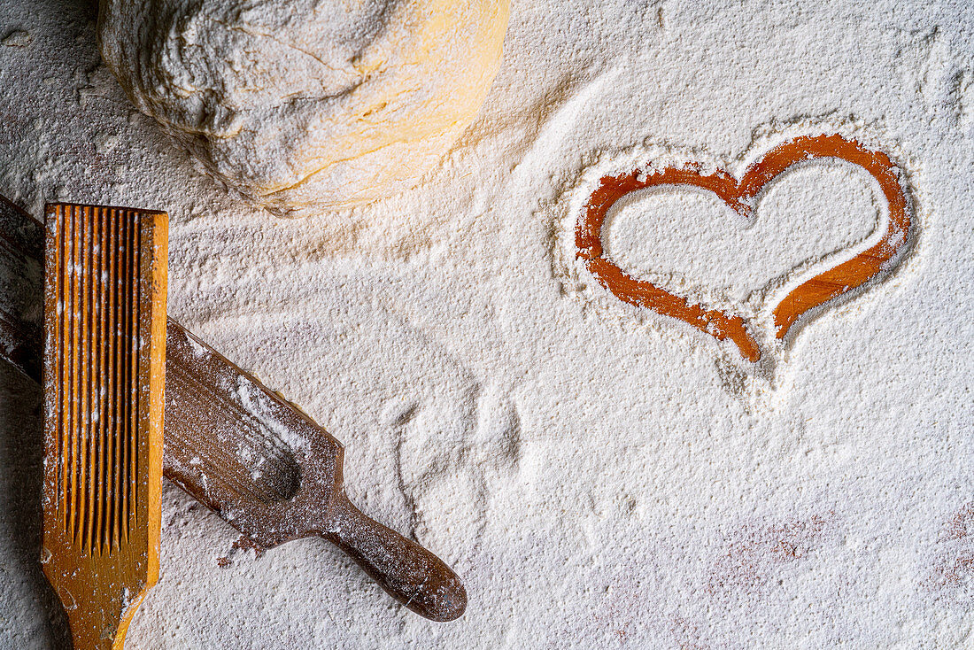 Heart in wheat flour and bunch of dough with wooden pasta board