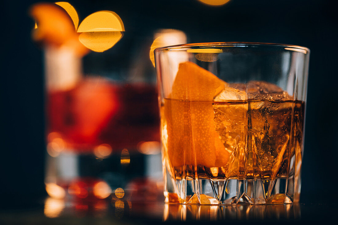 Old fashioned cocktail with orange slice and ice cubes