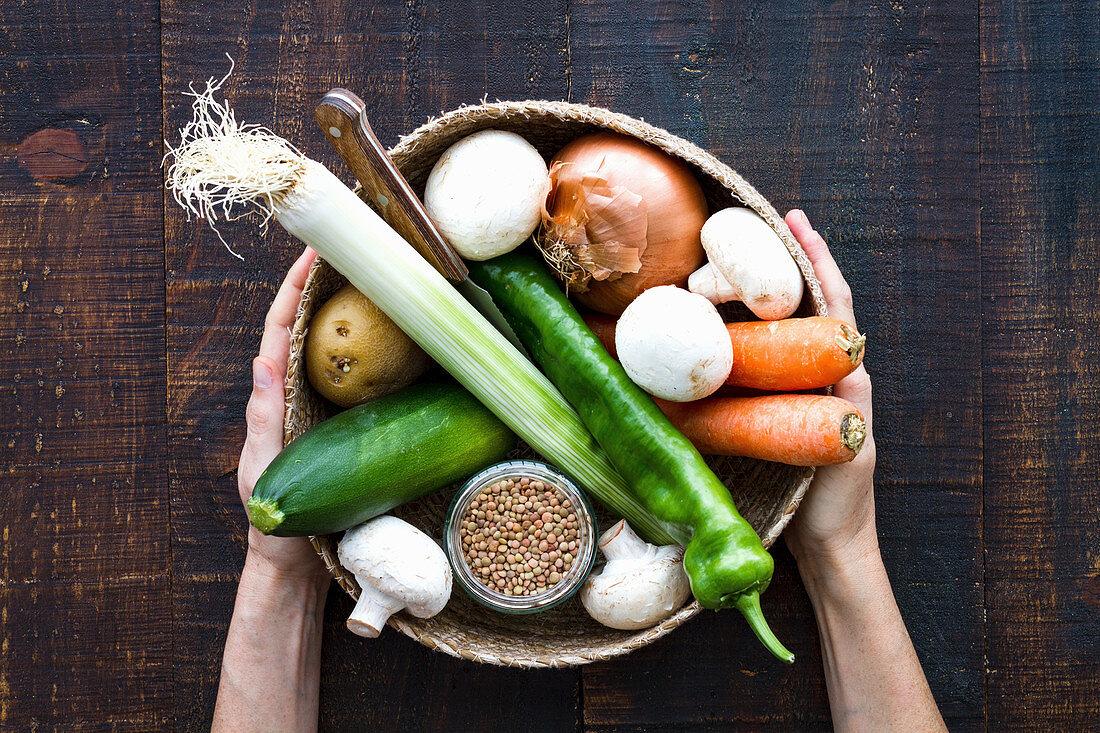 A basket with carrots, mushrooms, leek, pepper and jar of grains