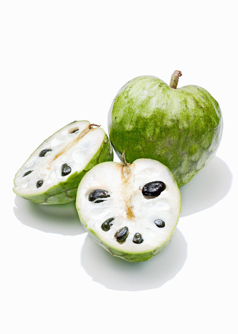 Cherimoya, whole and halved against a white background
