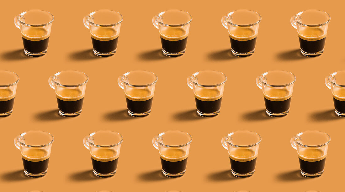Many cups of hot espresso in rows