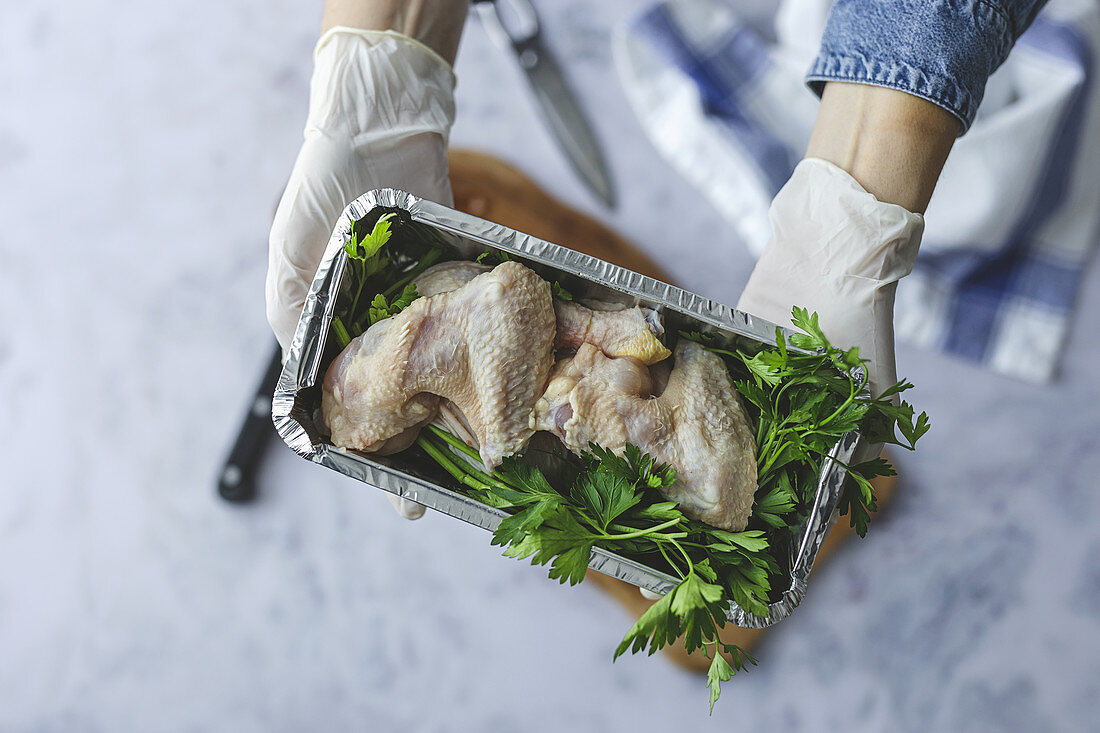 Hands with gloves hold takeaway container with raw chicken thighs