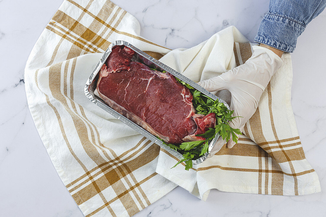 Hand with gloves holds takeaway container with raw steak