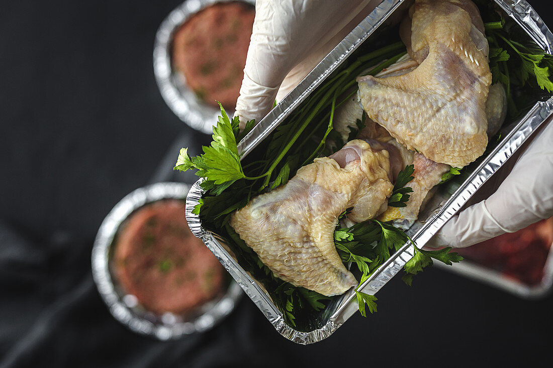 Hand with gloves hold takeaway container with raw chicken thighs