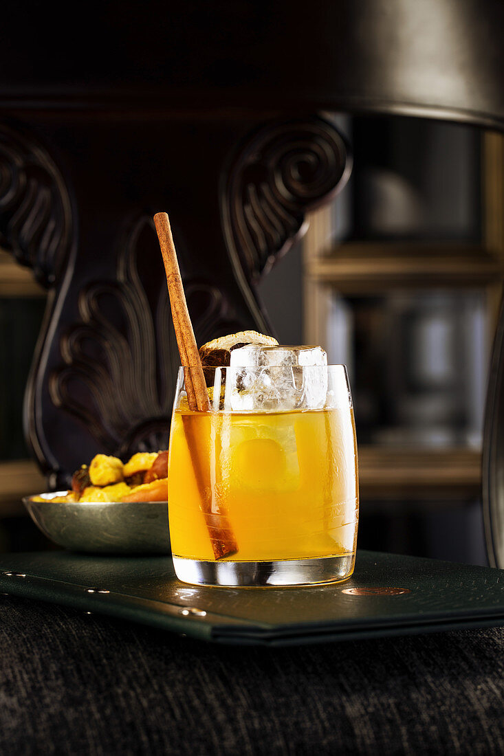 Yellow cocktail in a glass with cinnamon and orange