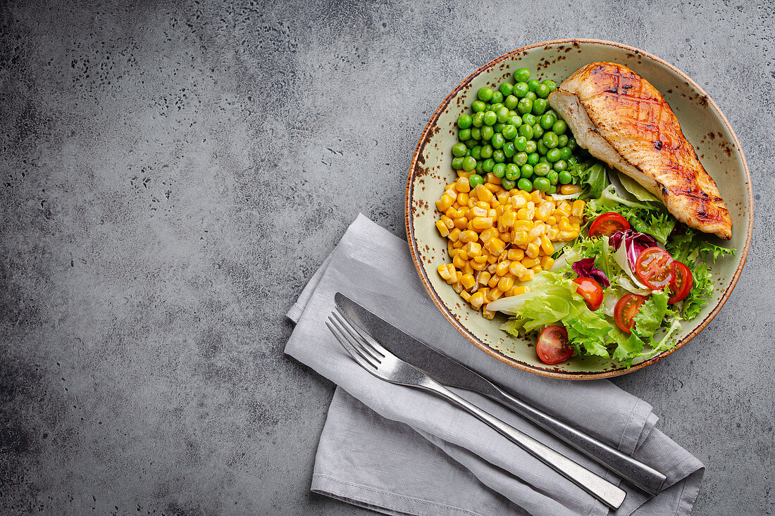 Baked chicken breast with fresh salad, green peas and corn