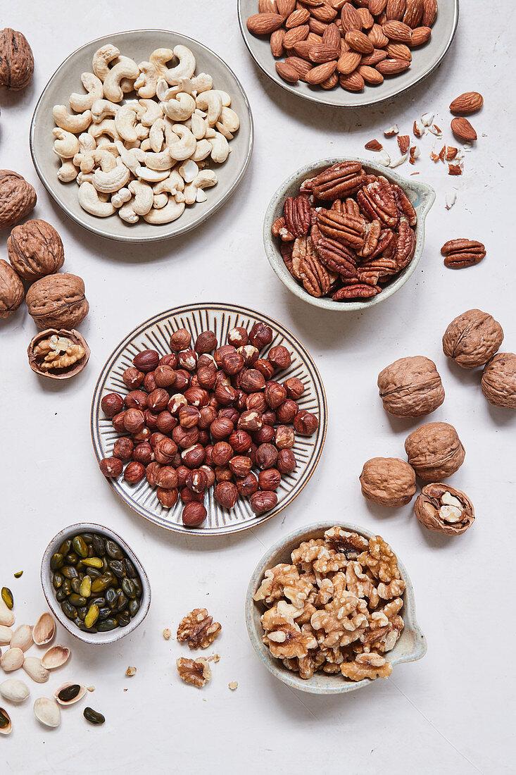 Verschiedene Nüsse in Schälchen und auf Tellern