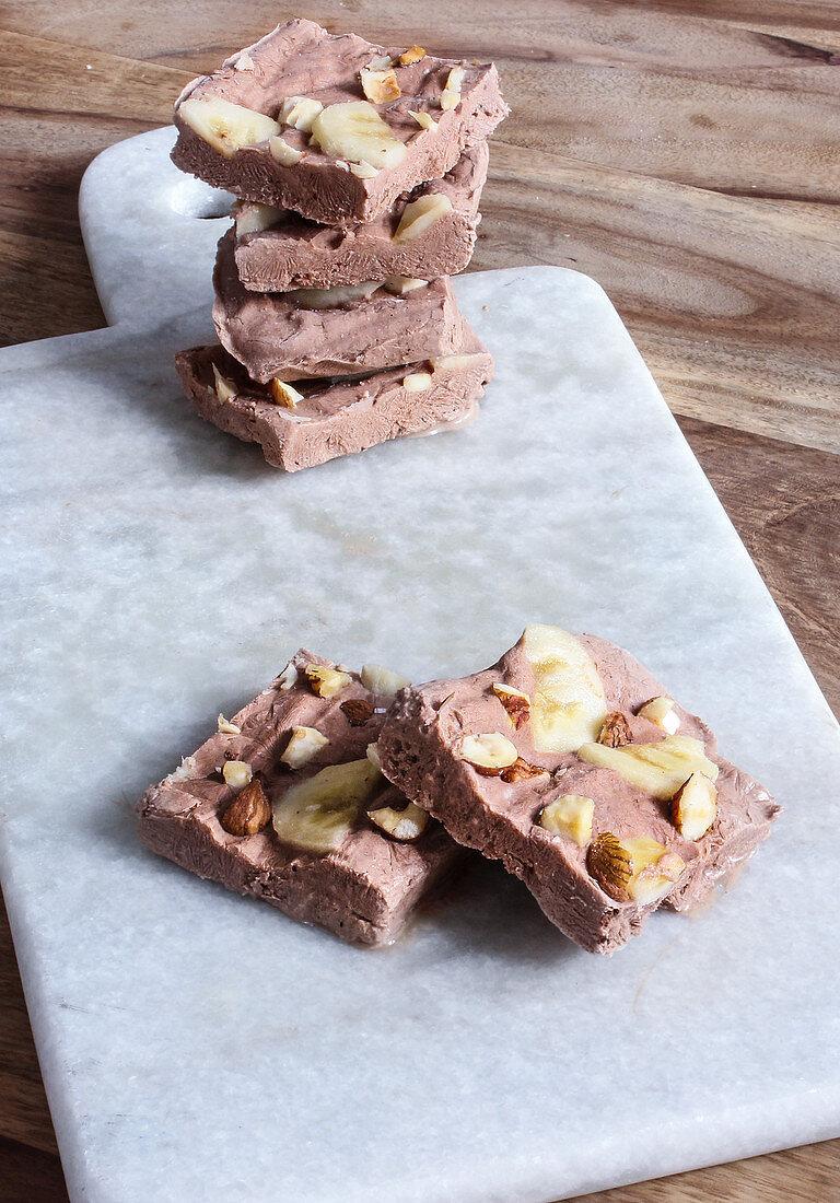 Frozen yoghurt bars with chocolate-coated banana and almonds