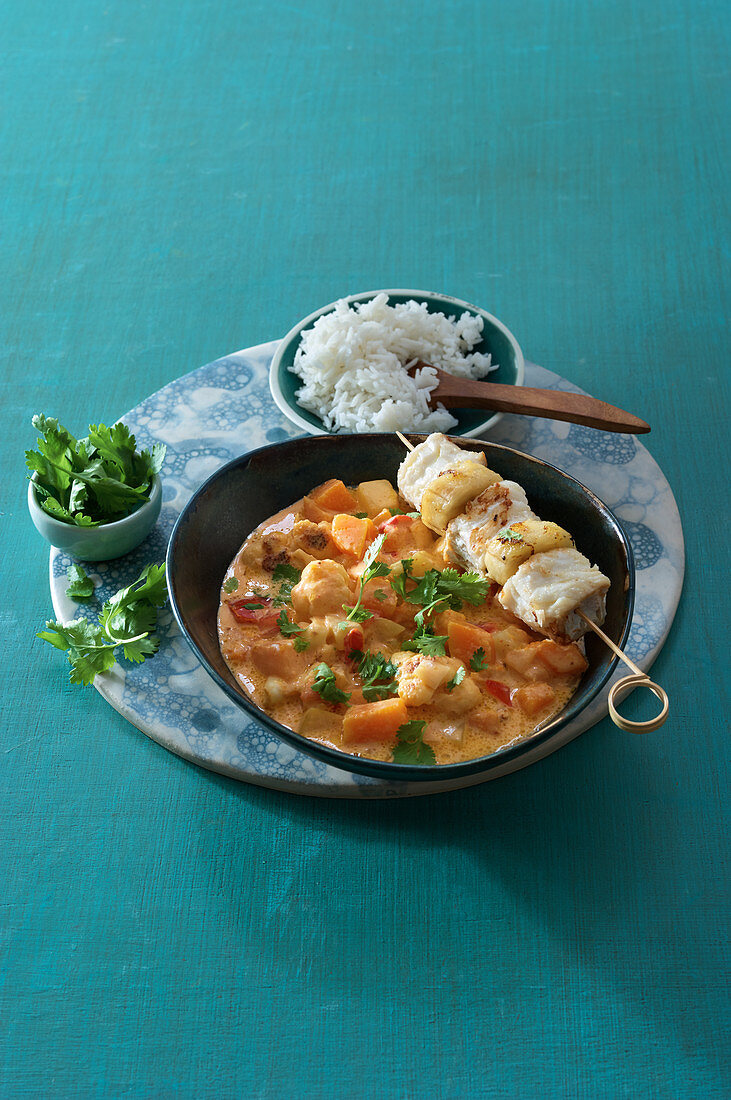 Pumpkin-coconut curry with fish skewer and rice