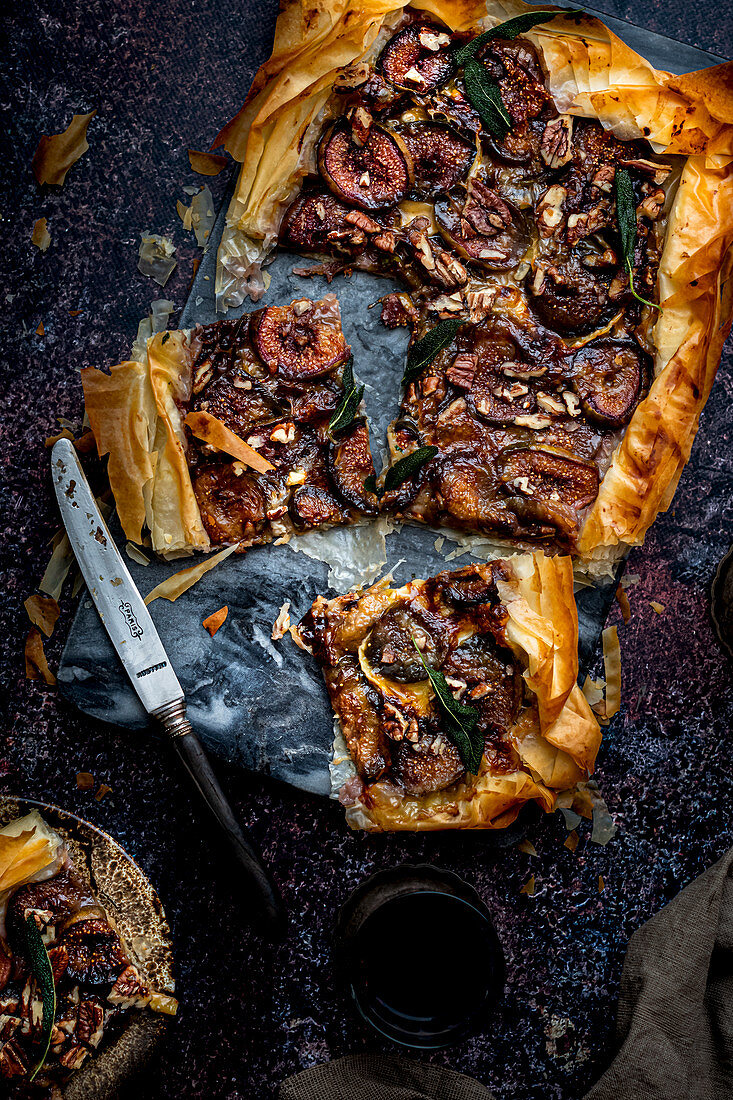 Fig tart in phyllo crust with blue camembert cheese, crispy sage and chopped nuts