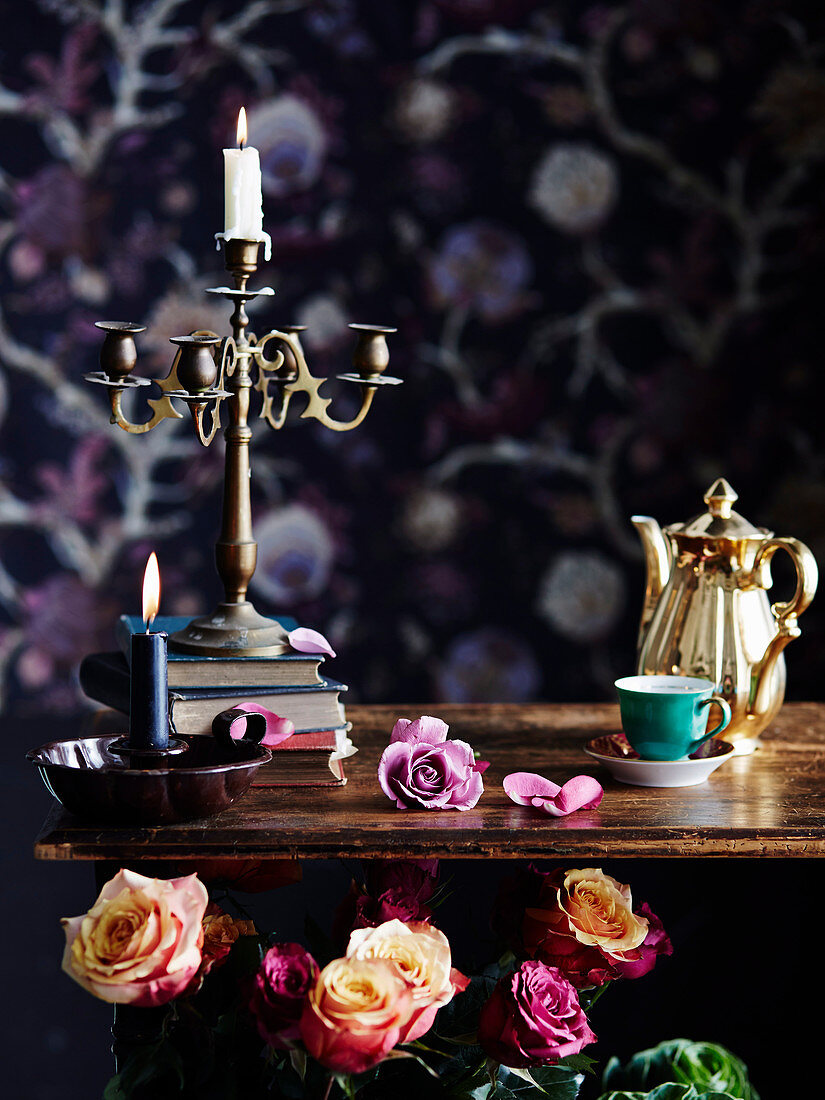 Candle in vintage candelabra and coffee dishes on wooden table